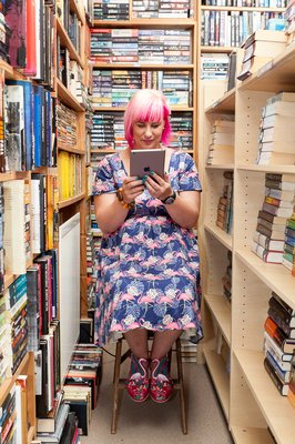Photo of poet Kate Fox looking at an IPad among the bookshelves